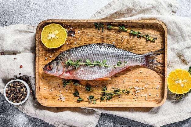 Surowy karaś na drewnianej tacy. ryby ekologiczne rzeczne. widok z góry