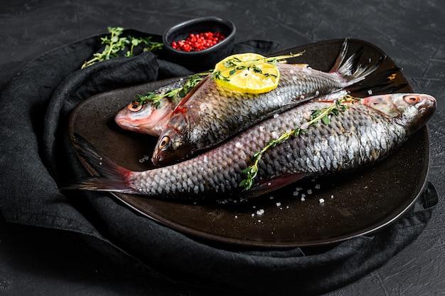 Surowy karaś z cytryną i tymiankiem na czarnym talerzu. ryby ekologiczne rzeczne. widok z góry