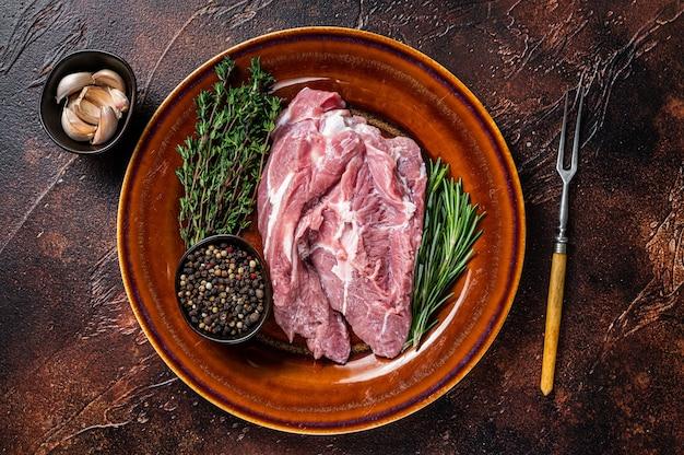 Surowy kawałek mięsa z łopatki wieprzowej z przyprawami na rustykalnym talerzu. ciemne tło. widok z góry.
