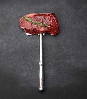 Surowy kawałek stek wołowy leżą na żelaznym nożu, czarne tło. klasyczny stek, widok z góry