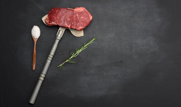Surowy kawałek steku wołowego leżą na żelaznym nożu, czarna powierzchnia. klasyczny stek, kopia przestrzeń