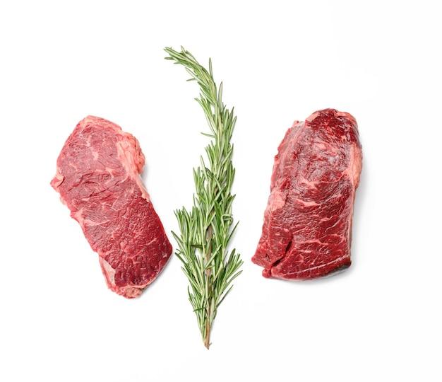 Surowy kawałek steku wołowego na białej powierzchni, klasyczny grill z polędwicy wołowej, widok z góry