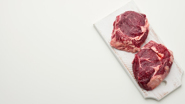 Surowy kawałek wołowiny ribeye na białym tle, kopia przestrzeń