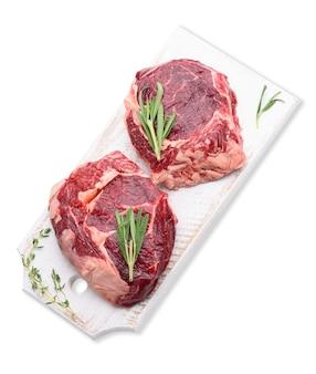 Surowy kawałek wołowiny ribeye z rozmarynem, tymianek na białej drewnianej desce do krojenia, widok z góry. jedzenie na białym tle