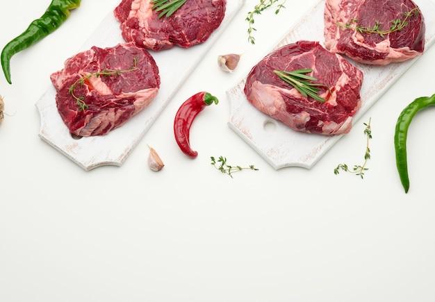 Surowy kawałek wołowiny ribeye z rozmarynem, tymiankiem na białym stole, widok z góry