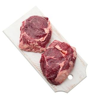 Surowy kawałek wołowiny ribeye z rozmarynem, tymiankiem na białym tle, widok z góry