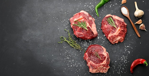 Surowy kawałek wołowiny ribeye z rozmarynem, tymiankiem na czarnym stole, widok z góry, miejsce na kopię