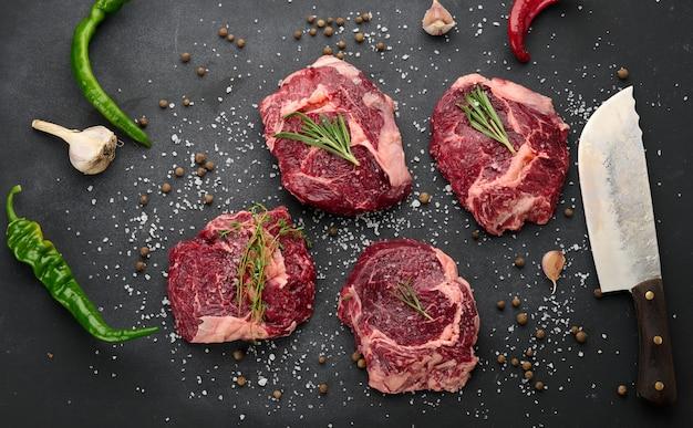 Surowy kawałek wołowiny ribeye z rozmarynem, tymiankiem na czarnym stole, widok z góry