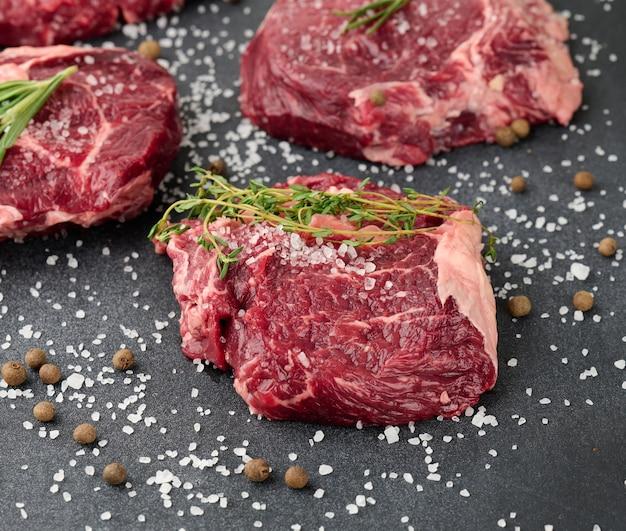 Surowy kawałek wołowiny ribeye z rozmarynem, tymiankiem na czarnym stole, z bliska