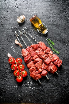 Surowy kebab na szaszłykach z pomidorami, czosnkiem i oliwą w butelce. na czarnej powierzchni rustykalnej