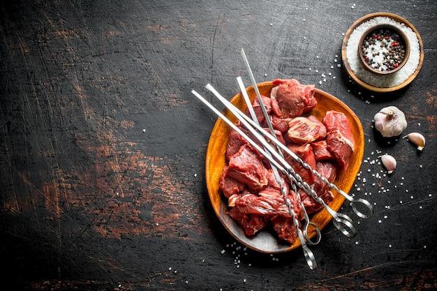 Surowy kebab na talerzu ze szaszłykami, przyprawami i czosnkiem. na ciemny rustykalny