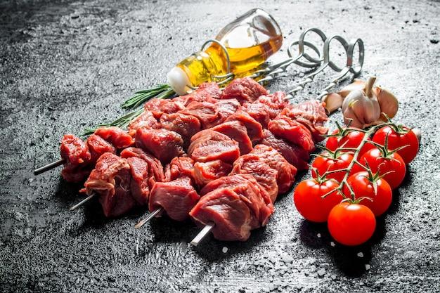Surowy kebab z pomidorami na gałęzi, oliwą i czosnkiem. na czarnej powierzchni rustykalnej