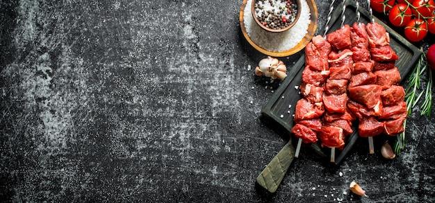 Surowy kebab z pomidorami, przyprawami i ząbkami czosnku. na rustykalnym