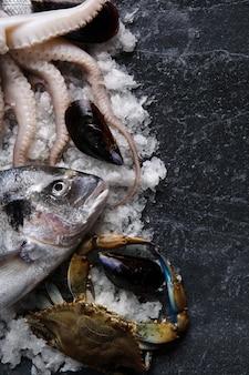 Surowy koktajl z owoców morza, dorado, krab błękitny i mątwy na lodzie