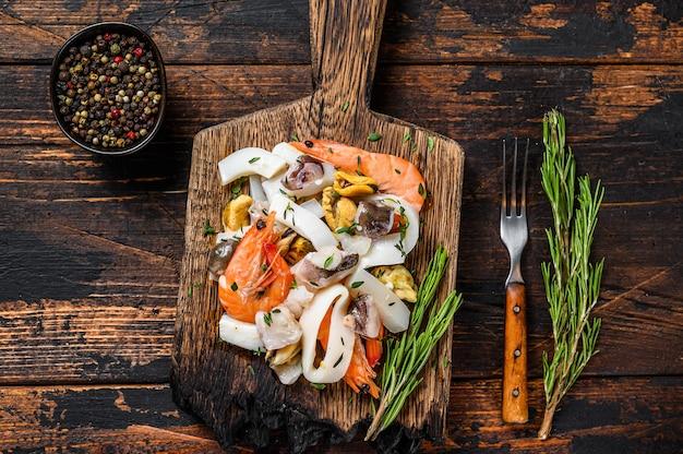 Surowy koktajl z owoców morza z krewetkami, małżami, kalmarem i ośmiornicą na desce do krojenia