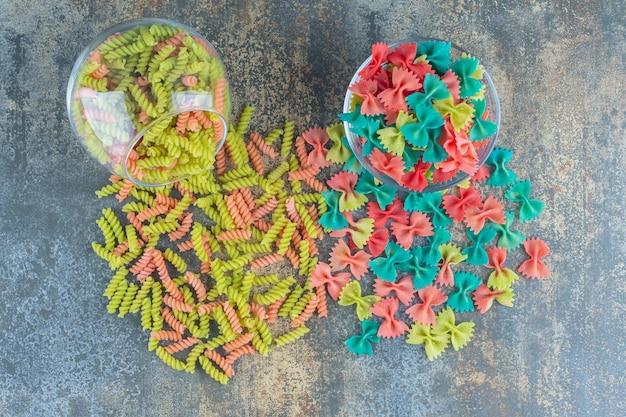 Surowy kolorowy makaron farfalle i fusilli, na marmurowej powierzchni.