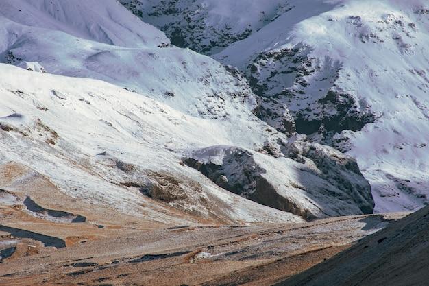 Surowy krajobraz gór skalistych pokrytych warstwami śniegu