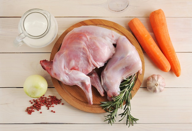 Surowy królik na drewnianej desce ze składnikami do duszenia mleka, cebuli, marchwi, rozmarynu