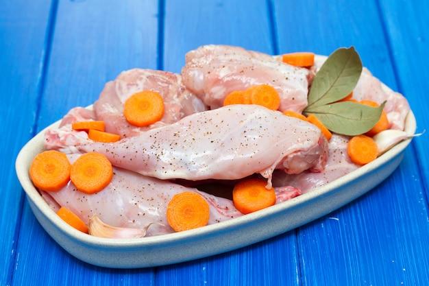 Surowy królik z marchewką na naczyniu