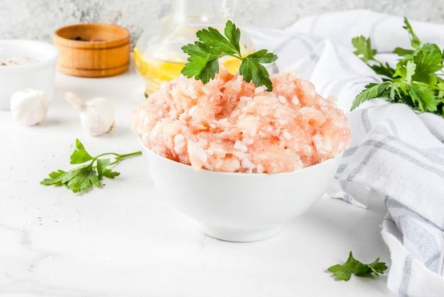 Surowy kurczak lub mięso mielone z indyka w białej misce, z olejem, przyprawami i ziołami