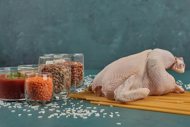 Surowy kurczak na drewnianej desce z fasolą i przyprawami.