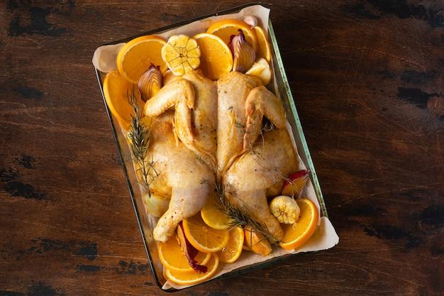Surowy kurczak w całości do domowego wypieku z cytryną, czosnkiem i pomarańczami na rustykalnym drewnie