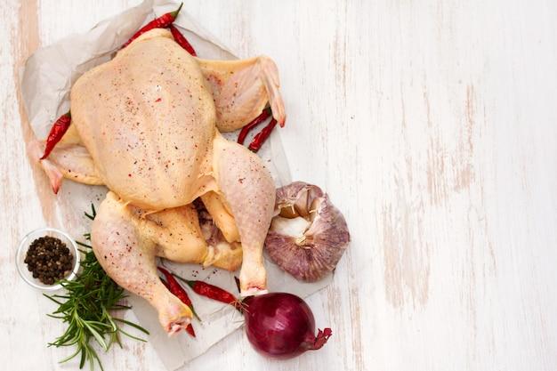 Surowy kurczak z ziołami i czosnkiem na drewnianej powierzchni