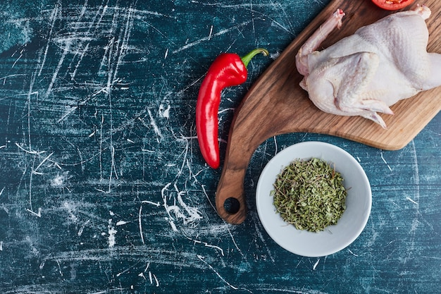 Surowy kurczak z ziołami i przyprawami.