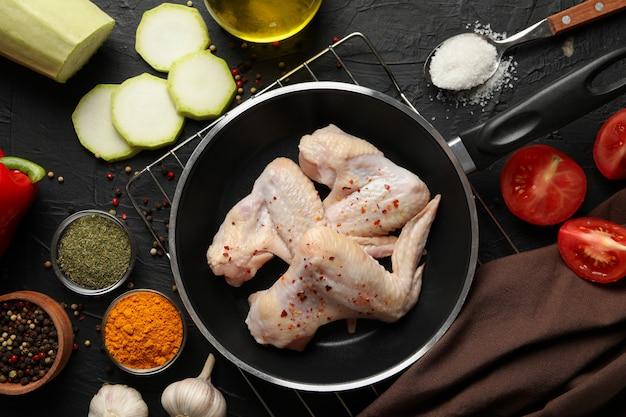 Surowy kurczaka mięso, pikantność na czerni i, odgórny widok. gotowanie kurczaka