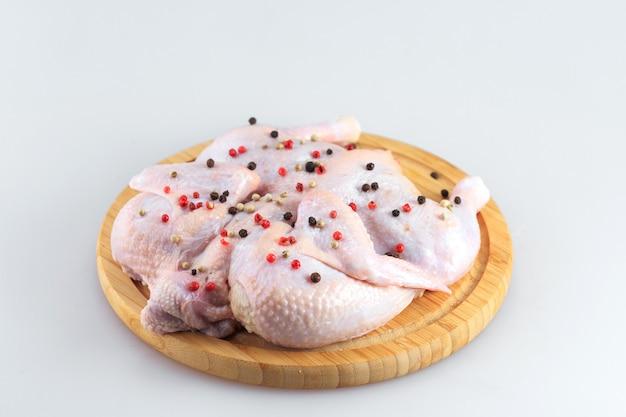Surowy kurczaka ścierwo na tnącej desce odizolowywającej na białym tle