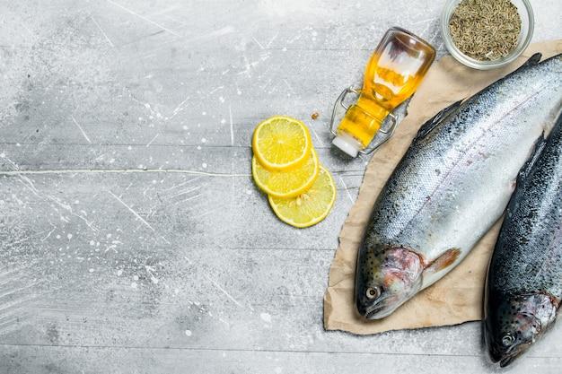 Surowy łosoś rybny z kawałkami cytryny, rozmarynem i przyprawami.
