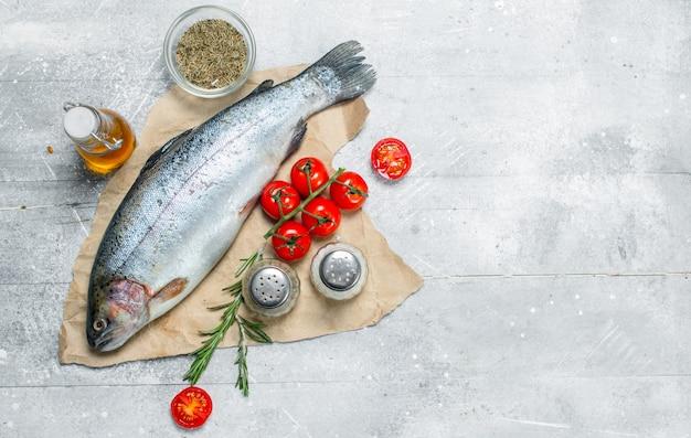 Surowy łosoś rybny z pomidorami, przyprawami i rozmarynem. na rustykalnym.