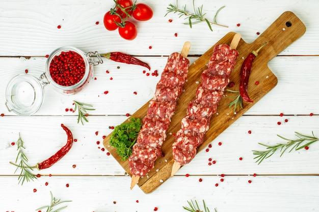 Surowy lula kebab na szaszłykach z przyprawami na desce