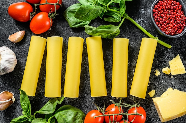 Surowy makaron cannelloni. kuchnia włoska. składniki do gotowania: bazylia, pomidorki koktajlowe, parmezan, czosnek