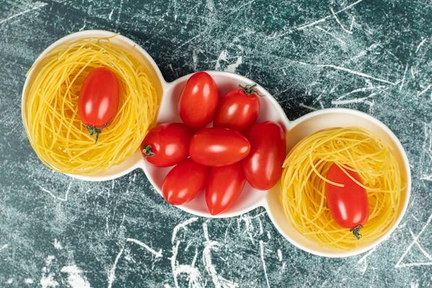 Surowy makaron capellini i pomidory w naczyniu, na niebieskiej powierzchni