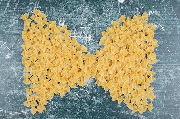 Surowy makaron farfalle uformowany jak wstążka na niebieskim tle. wysokiej jakości zdjęcie