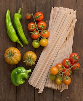Surowy makaron fettuccine i warzywa na podłoże drewniane