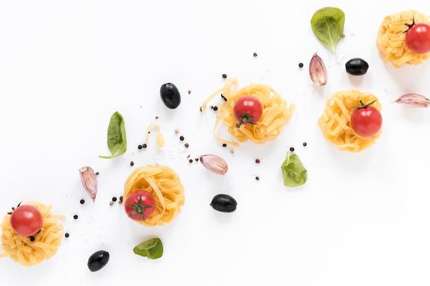 Surowy makaron fettuccine; pomidor wiśniowy; czarna oliwka; ząbek czosnku i liści bazylii samodzielnie na białym tle