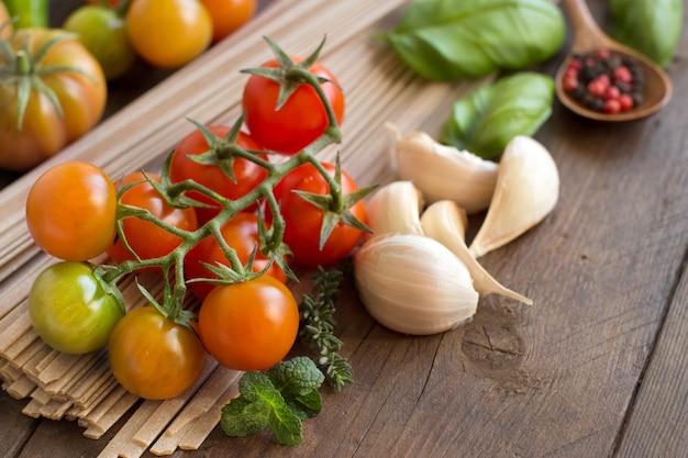 Surowy makaron fettuccine, warzywa i zioła na podłoże drewniane