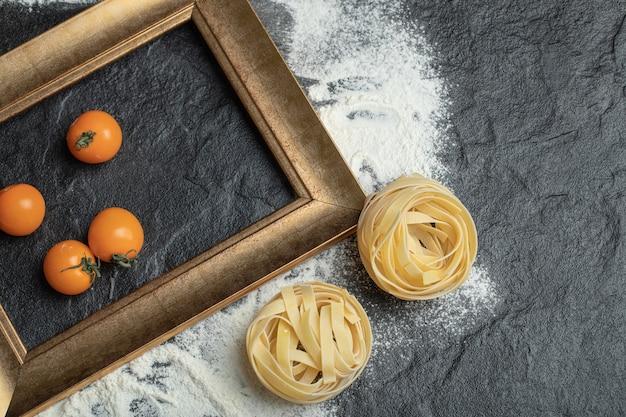 Surowy makaron gniazdowy z mąką i pomidorkami koktajlowymi.