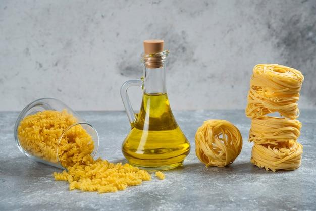 Surowy makaron gniazdowy ze szklaną butelką oleju.