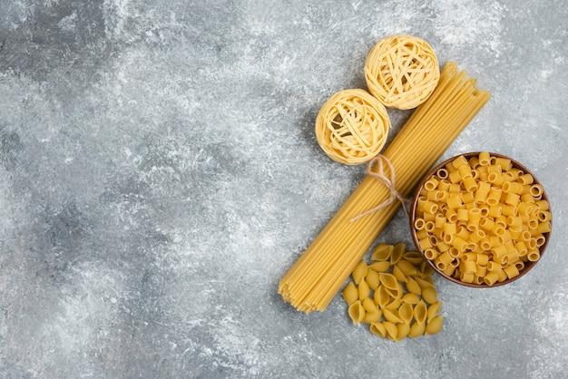 Surowy makaron i odmiany spaghetti na marmurowym stole.