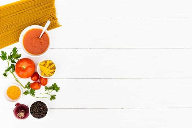 Surowy makaron i smakowity składnik nad białym drewnianym stołem