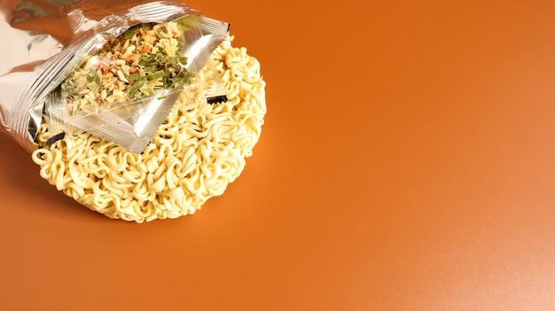 Surowy makaron instant z nienazwanego opakowania foliowego bez zbliżenia na nazwę z przyprawami i masłem. makaron, do przygotowania którego wystarczy zalać wodą. skopiuj miejsce.