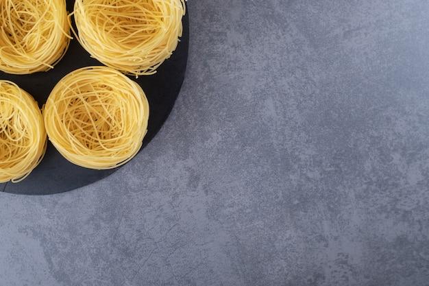 Surowy makaron jajeczny na czarnej tablicy.
