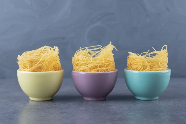 Surowy makaron jajeczny w kolorowych miseczkach.