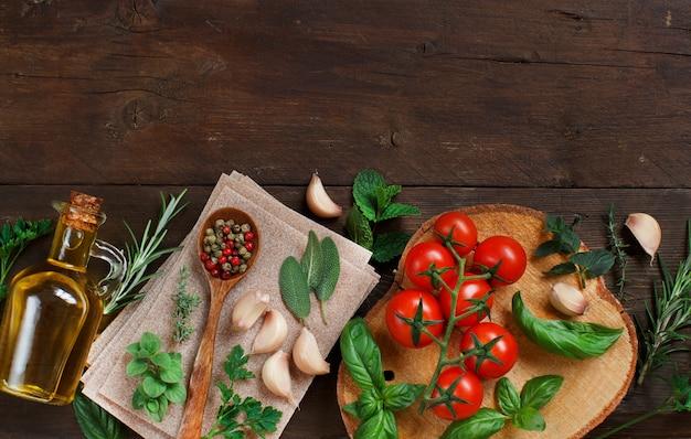 Surowy makaron lasagne, warzywa i zioła na podłoże drewniane