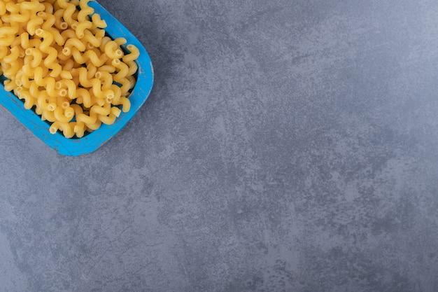 Surowy makaron łokcia na niebieskim talerzu.