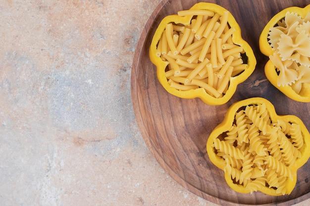 Surowy makaron na pieprzu na drewnianym talerzu.