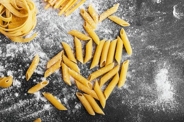 Surowy makaron na posypanej mąką powierzchni.